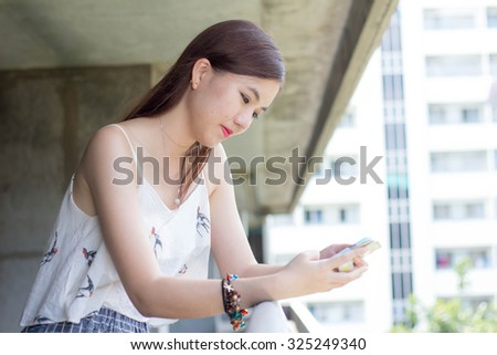 very happy thai adult beautiful girl read message on Smartphone.
