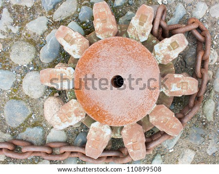 Very heavy and rusting dock chains and cog whee to real in and release or anchor a vessel to the bollards - stock photo