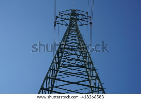 Very high electricity pylon during the sunny day with bright sun and blue sky
