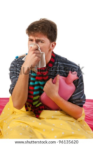 Very ill man is sitting in his bed with warm water bottle and thermometer - stock photo
