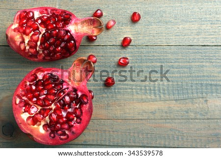 very juicy and big and delicious pomegranate in the section on wooden background isolated - stock photo