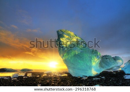 Very large and beautiful chunk of ice at the beach at Jokulsarlon, Iceland, at sunset in winter. HDR - stock photo