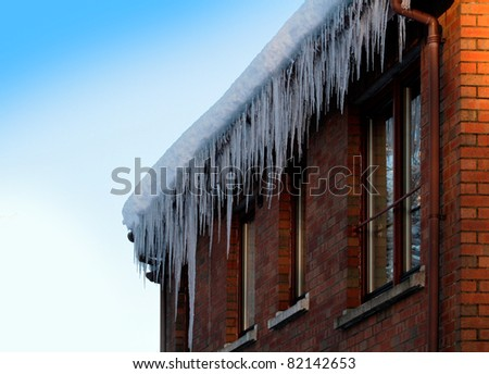 Very large icicles on the edge of a typical brick house in the UK - stock photo