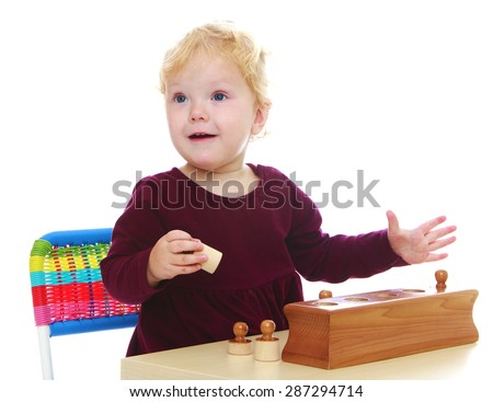 Very little girl in the history of the kindergarten is studying montessori materials-Isolated on white background - stock photo