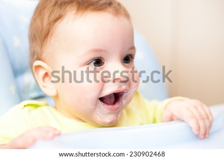 very little kid eats fresh tasty nutritious curds on highchair - stock photo