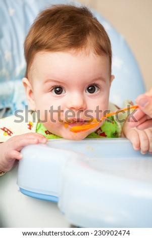 very little kid eats fresh tasty nutritious curds on highchair - stock photo