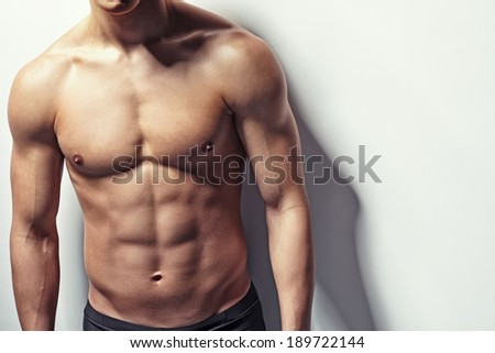 Very muscular and sexy torso of young man with copy space - stock photo