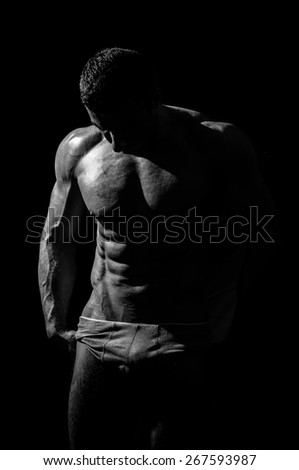 very muscular handsome athletic man on black background, naked torso