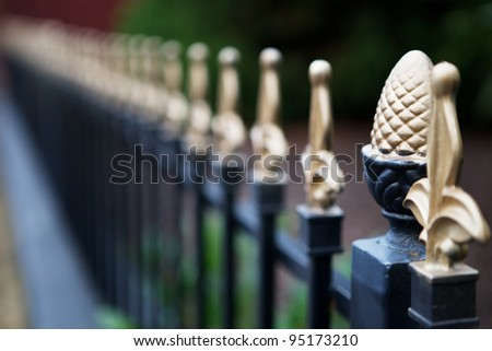 Very narrow dept of field focus on the pineapple post with gold tipped spikes diminishing to very soft focus - stock photo