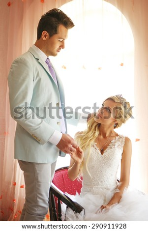 Very nice and bright bride sits on a chair next to the groom