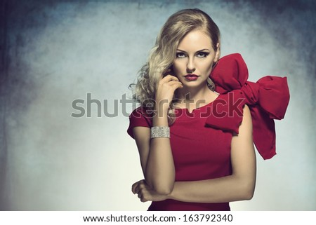 very nice sexy girl in red , with big bow on shoulder . creative hair style looking seriously in camera - stock photo