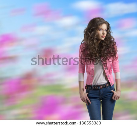 very nice young girl brunette with wavy and volume hair wears blue jeans and pink jacket, colorful background - stock photo