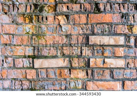 Very old almost ruined and weathered brick wall with moss - stock photo