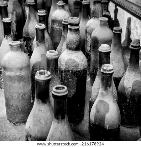 Very old and dusty bottles stacked in warehouse in black and white - stock photo