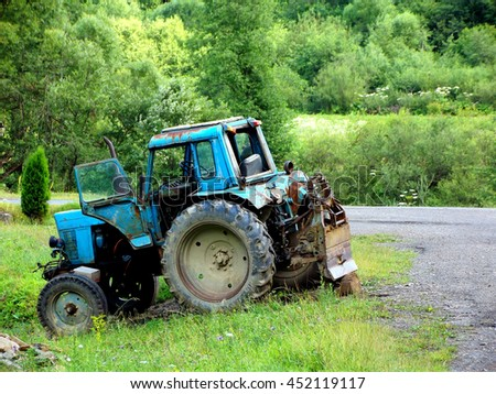 Very old blue tractor without trademark on the roadside