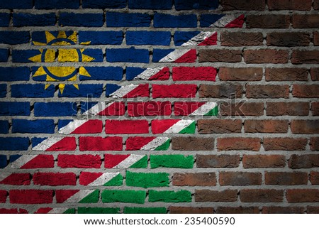 Very old dark red brick wall texture with flag - Namibia - stock photo