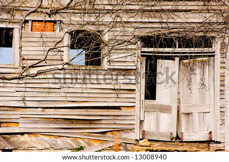 Very old, dilapidated buidling with door and windows,  Building has been covered with vines.  Symbol of decay, neglect or the passage of time etc. - stock photo