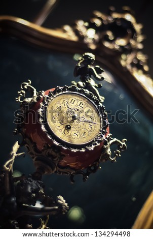 Very old fancy antique brow clock front of the mirror - stock photo