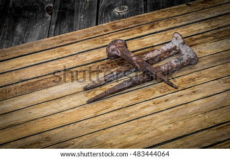 very old large nails on a beautiful wooden background, rusty nails, there is a place for text