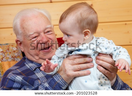 Very old man holding little baby - stock photo