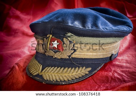 Very old military cap, possibly russian, on red background - stock photo