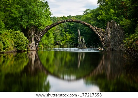 Very old stone bridge over the quiet lake with its reflection in the water, long exposure