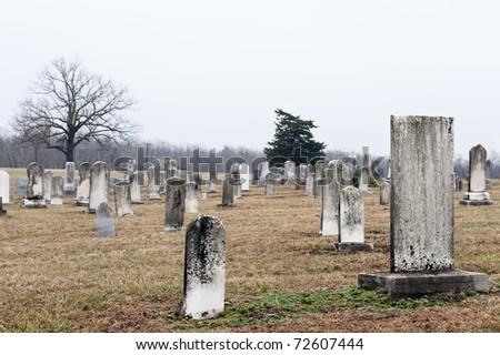 Very old tombstones in a country church graveyard, selective focus on large tombstone near camera - stock photo