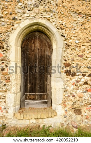 Very old wooden church door and aged stone frame - stock photo