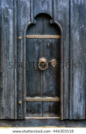 Very old wooden door in black with rusty iron lock and handle. - stock photo