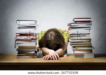 Very overworked female student at a table with lots of books - stock photo