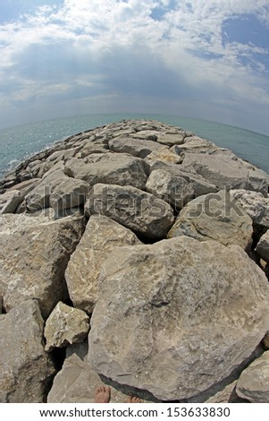 very picturesque seaside rocks and breakwaters photographed with the fisheye lens - stock photo
