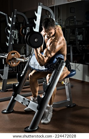 very power athletic guy bodybuilder,  execute exercise with  dumbbells, on Scott's bench - stock photo
