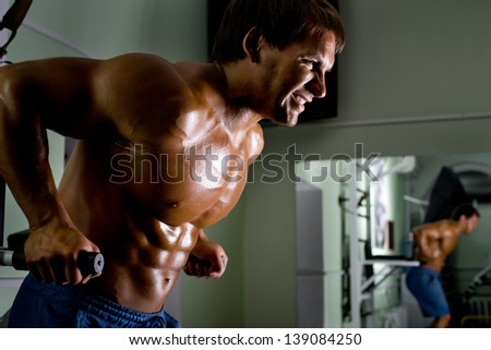 very power athletic guy ,  execute exercise on parallel bars, in sport hall - stock photo