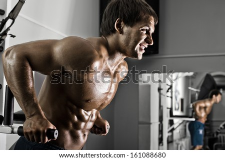 very power athletic guy ,  execute exercise on parallel bars, workout  in sport hall - stock photo