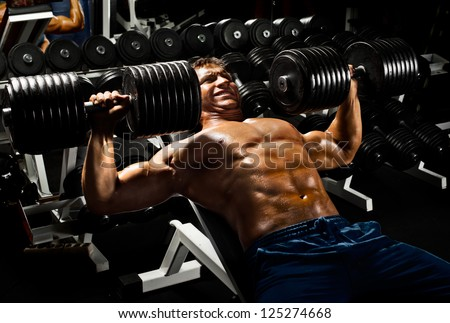 very power athletic guy ,  execute exercise press with  dumbbells, in sport hall - stock photo