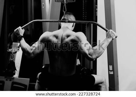 very power athletic guy , execute exercise tightening on horizontal bar, in sport-hall,  - stock photo