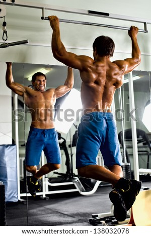 very power athletic guy ,  execute exercise tightening  on horizontal bar, in  sport-hall, glamour light - stock photo