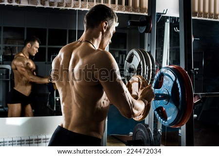 very power athletic guy ,  execute exercise with  weight - stock photo
