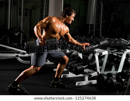 very power athletic guy ,  execute  traction with  dumbbells, exercise on broadest muscle of back, in sport hall - stock photo