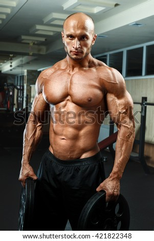 very power athletic young guy standing in gym with dumbbells and lokking at camera