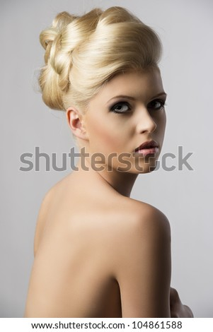 very pretty blonde woman with elegance hair style, she is turned at three quarters at right and looks in to the lens with serious expression - stock photo
