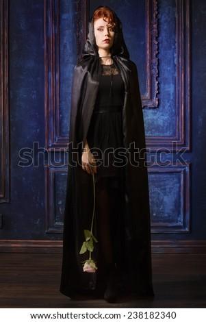 Very pretty woman vamp in the dark interior - stock photo