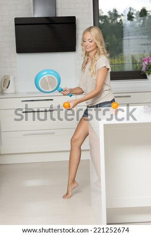 very pretty young blond girl in shorts playing tennis in funnny way , with a pan and an orange fruit in a modern kitchen - stock photo