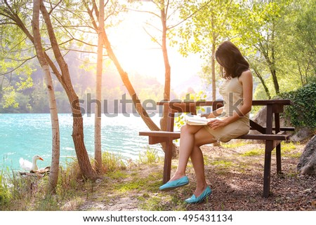 Very relaxing time for a people. There is one happy woman at the edge of the lake.