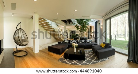 Very roomy ground floor of a contemporary designer house, with a large black lounge and a hanging chair - stock photo
