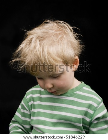 Very sad little boy on black background. Boy have blond hair and a bit of dirt on face