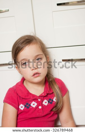 very sad little girl sitting on a floor and looking away - stock photo