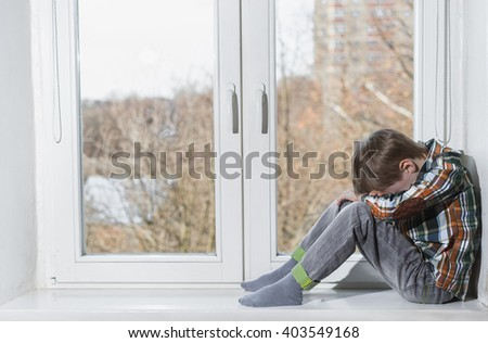 Very sad young boy sitting alone in window and hide his face in hands. - stock photo