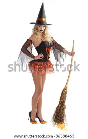 very sexy and beautiful young woman with black and orange witch dress ready for flying away with broom in her hand - stock photo
