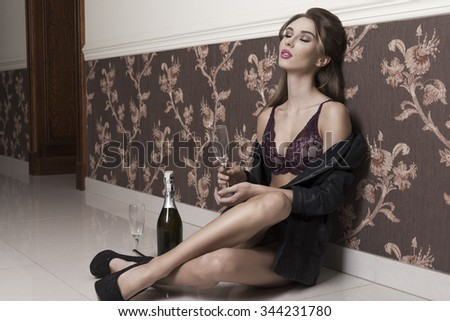 very sexy female with open jacket and lingerie sitting in indoor portrait of floor with relaxed expression and champagne for toast. New year party   - stock photo